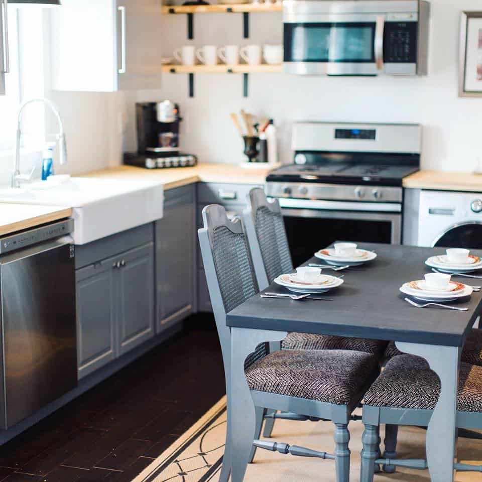 Kitchen and dining area of a Tuff Shed tiny house with a full stove and kitchen sink