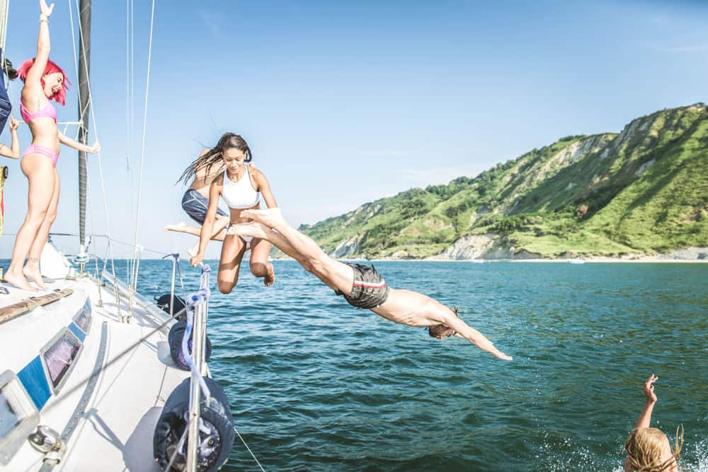People jumping off a liveaboard boat, which has a higher sailboat price than smaller boats