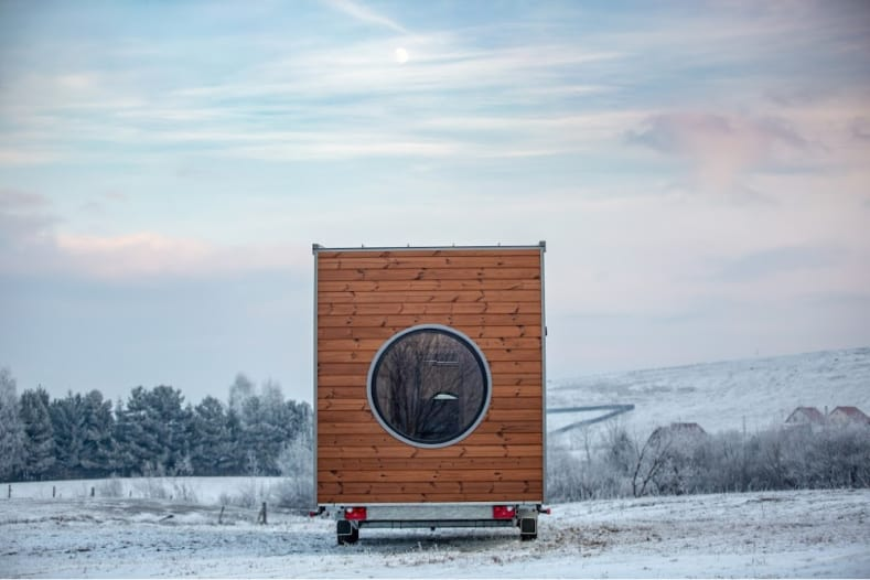 Tiny home on wheels parked in a field, surrounded by a snowy white landscape