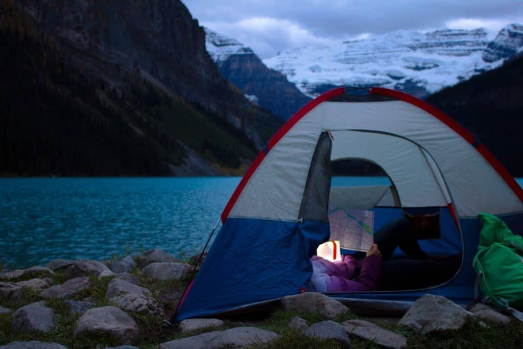 Best solar camping lantern lighting up the inside of a tent while someone reads a map
