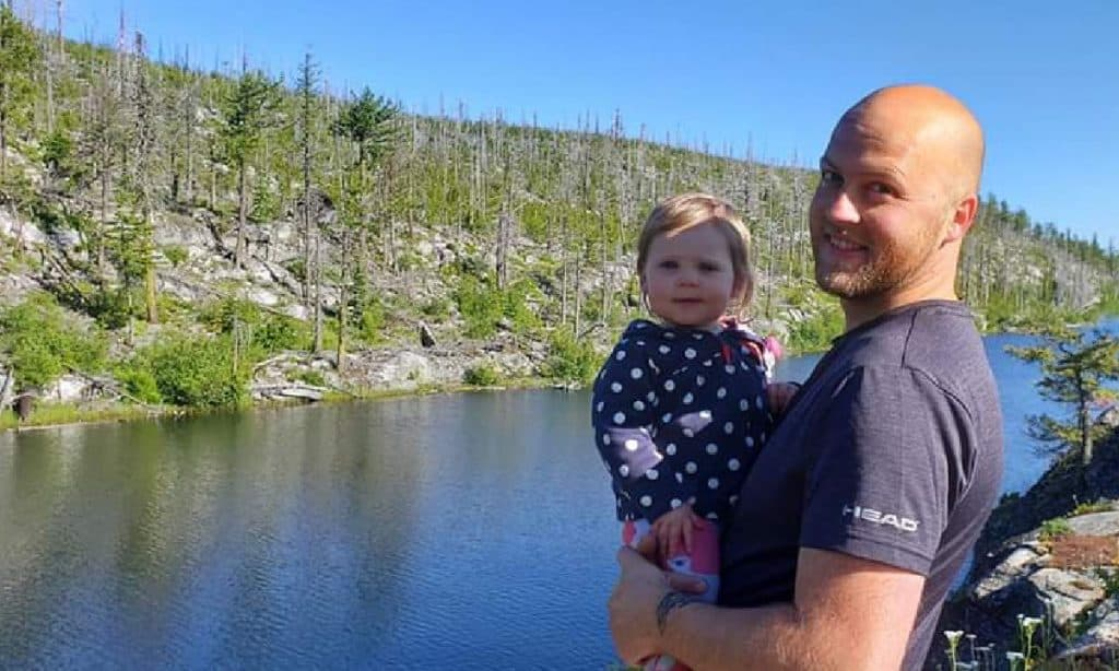 Glen, who started a bookkeeping business, with his daughter near a lake