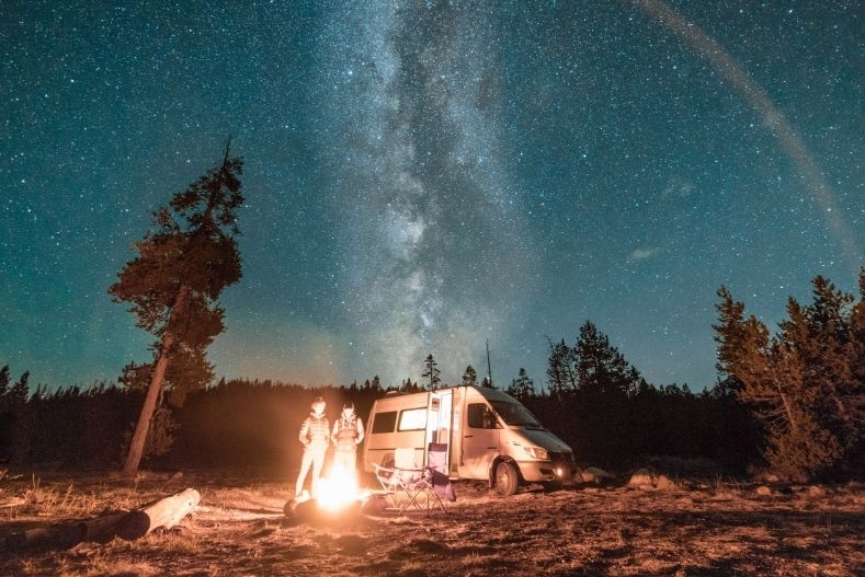 Used campervan near a campfire under the stars