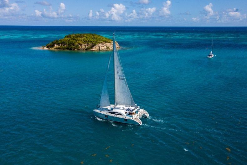 Catamaran vs Monohull: Catamaran sailing near an island