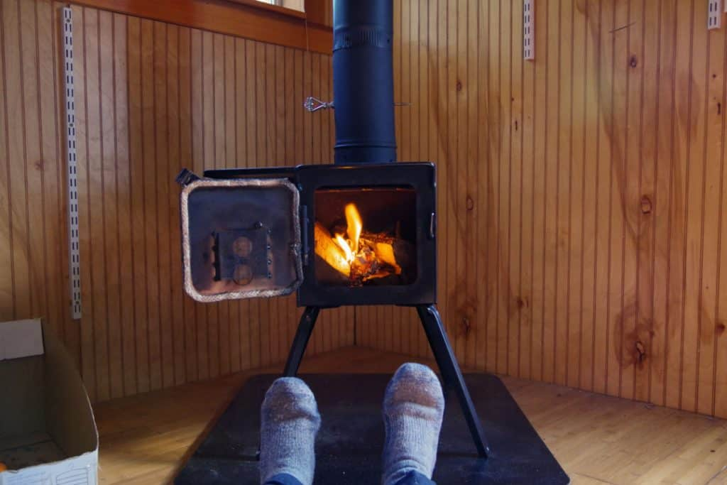 Person enjoying a tiny house wood stove, a great tiny house heater option