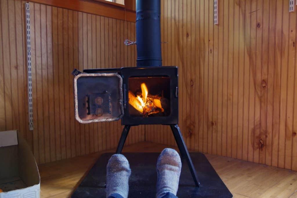 Person enjoying a tiny house wood stove, a great tiny house heater option