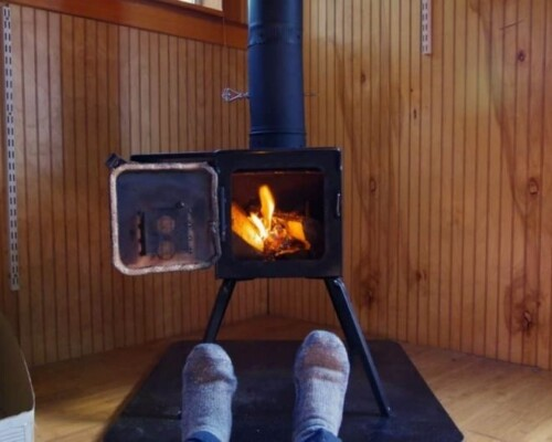 man sitting in front of a tiny house wood stove