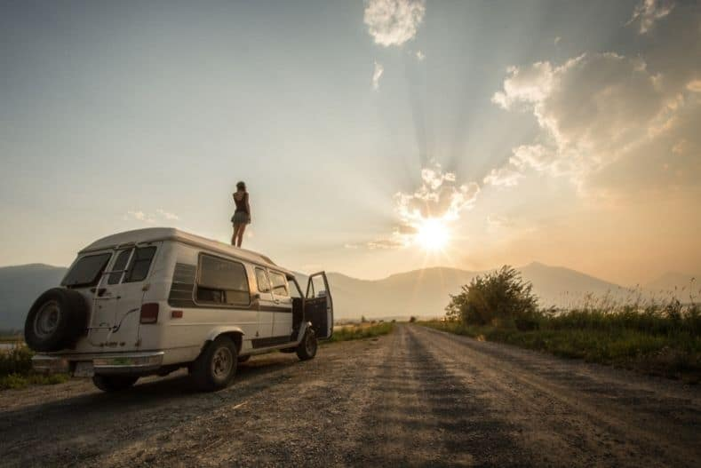 Woman stands on top of used camper van watching sunset