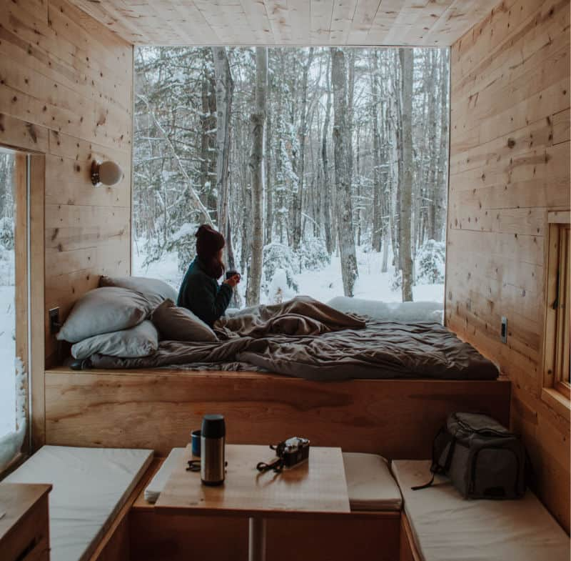 Woman sitting in a bed in a tiny house looking outside - a time when a tiny house heater is important