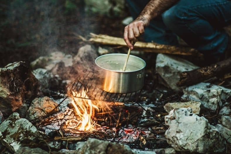 Man stirring water in a pot over a campfire