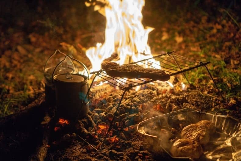 Steak cooking over a campfire