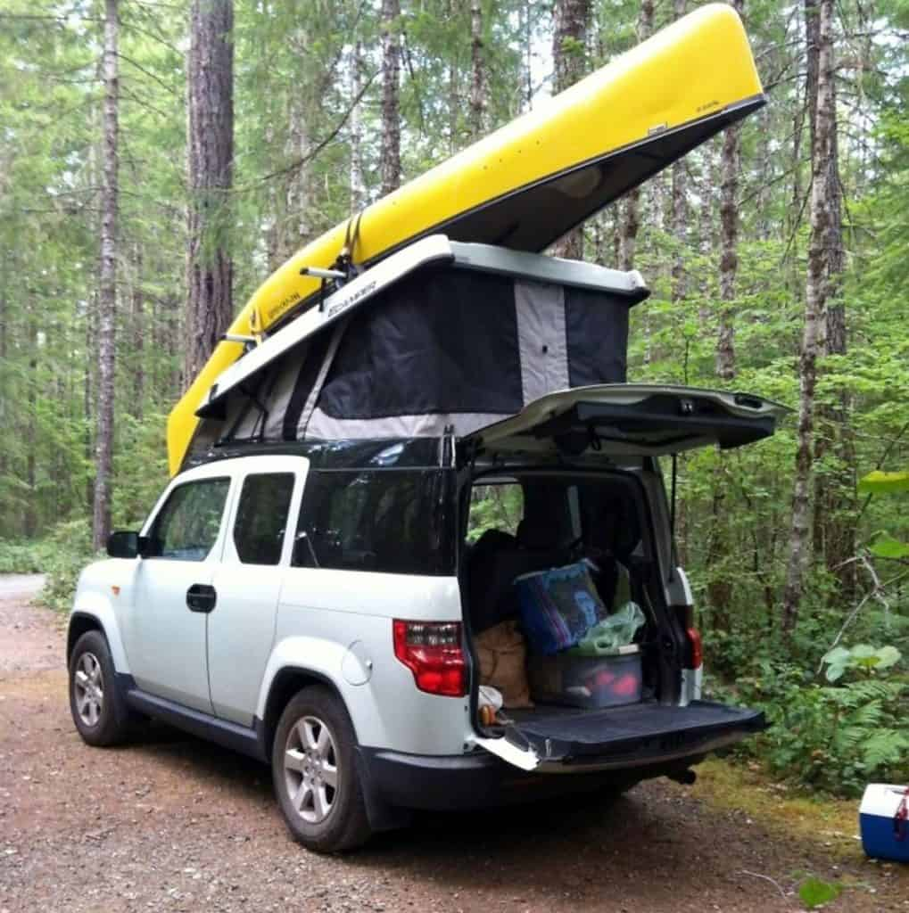 Honda Element camper with a pop top, kayak and gear in the truck