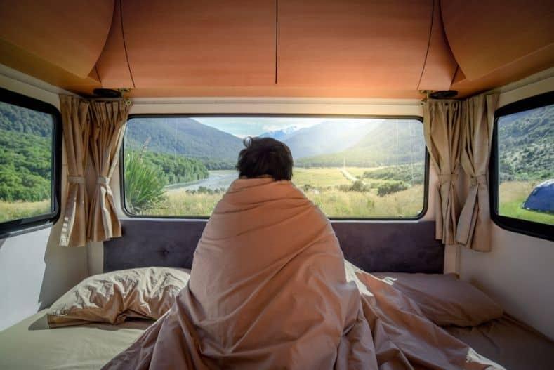 Man on best camper van mattress bundled in blanket