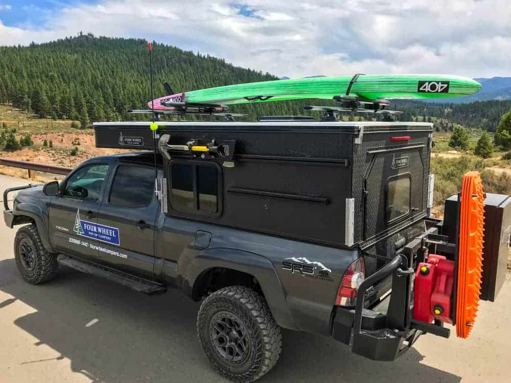 Project M super lightweight pop up truck camper on the back of a pickup with a surfboard on top