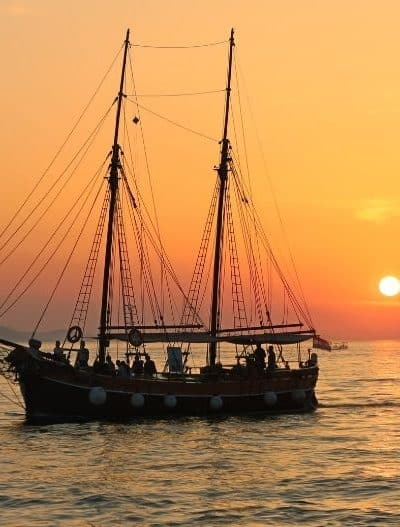Sailboat with two masts sails at sunset
