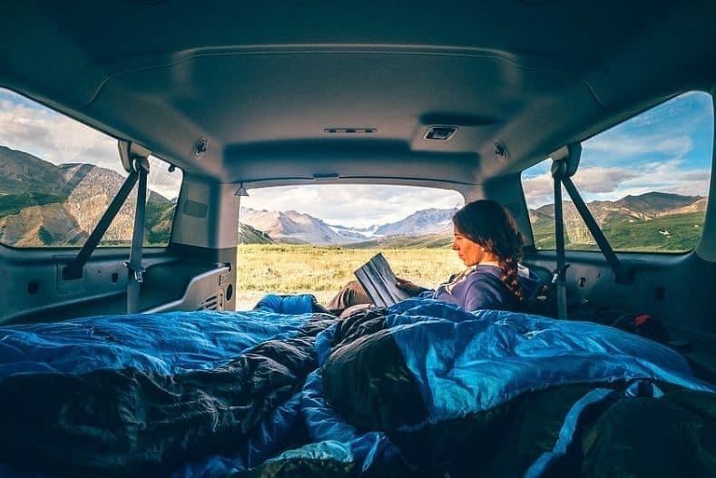 Woman reads in back of van on top of van life mattress
