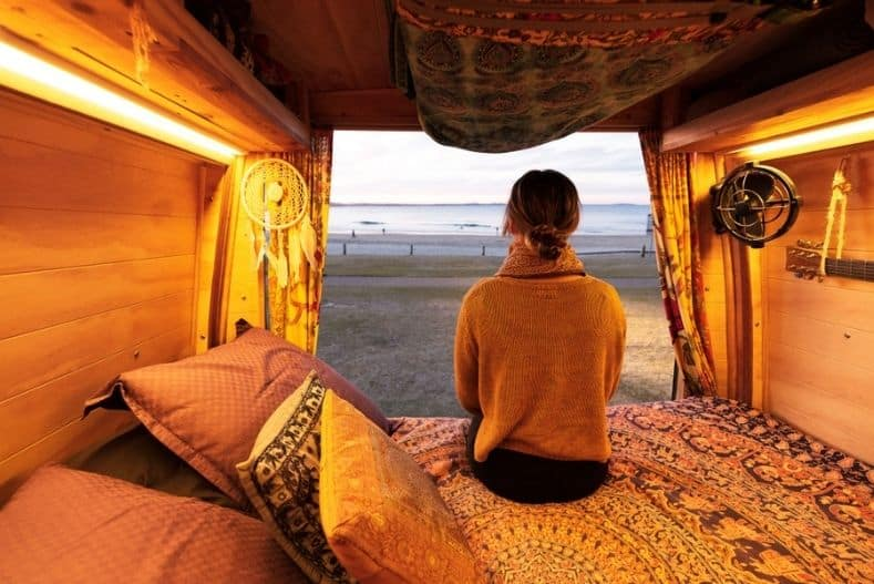 Woman sits on campervan bed mattress with bohemian blanket