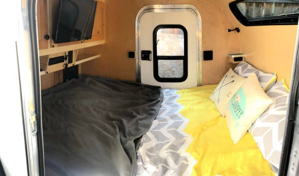Comfortable bed and TV inside this teardrop camper interior