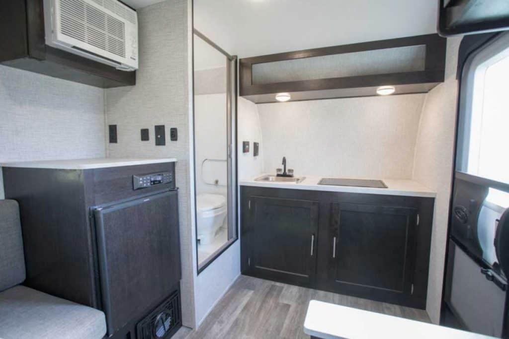 Teardrop camper interior with kitchen, wet bath and fridge