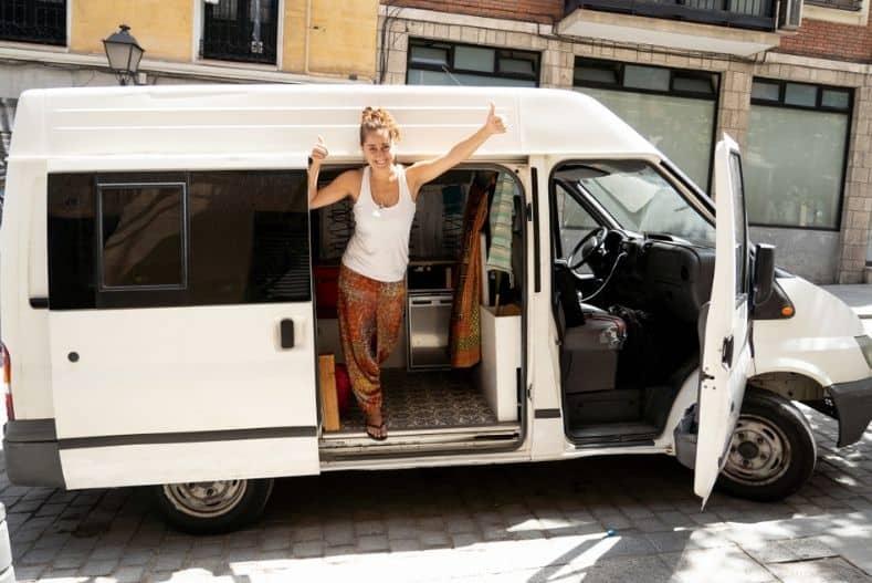 Woman standing in van door giving a thumbs up
