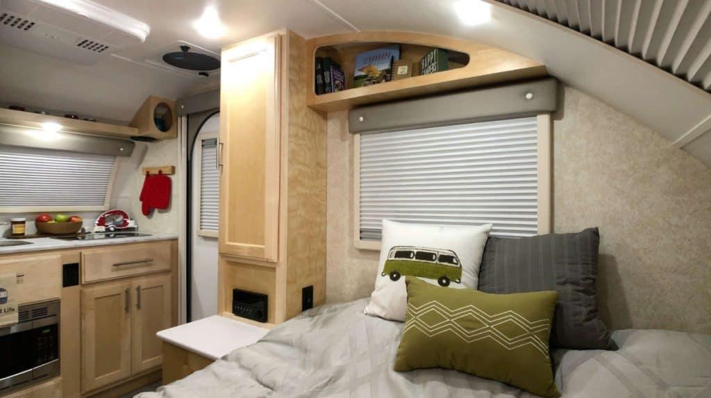 Teardrop trailer interior with comfortable bed, stargazer window and indoor kitchen.