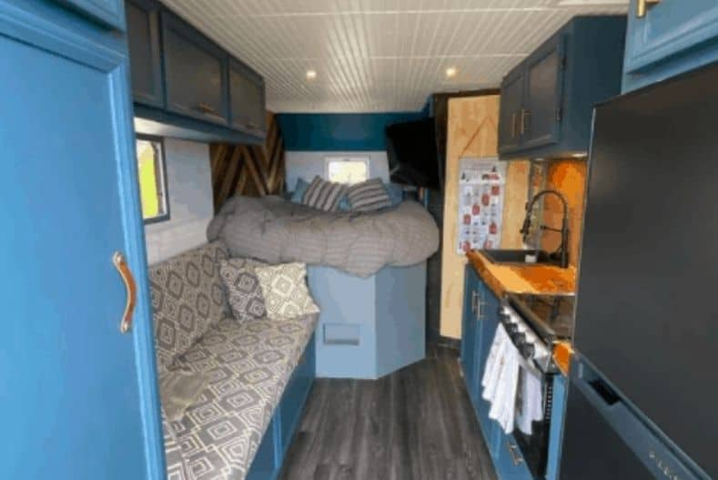 Luke and Sarah's box truck conversion interior with bed, couch and kitchenette