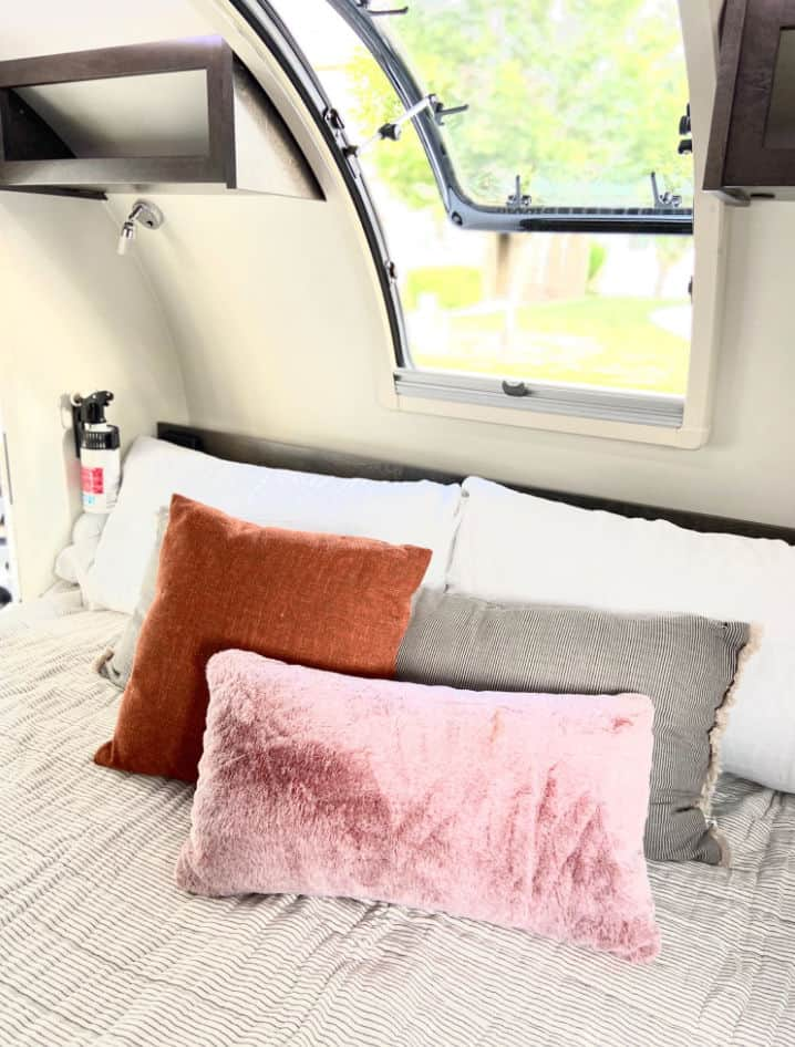 Teardrop camper interior with bed, pillows and stargazer windows.