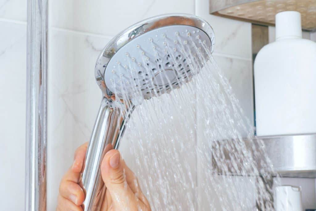 A showerhead with a hand holding it - showering while living on a sailboat is tricky!