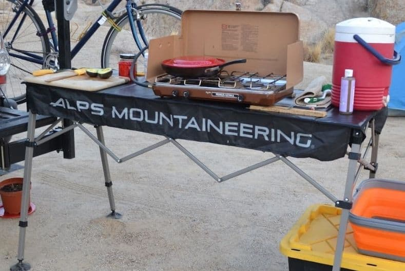 A camp table set up with a camping stove - an essential part of your truck camping accessories