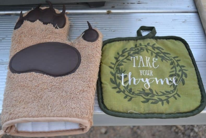 Two cute potholders on a folding table, perfect as truck camper accessories