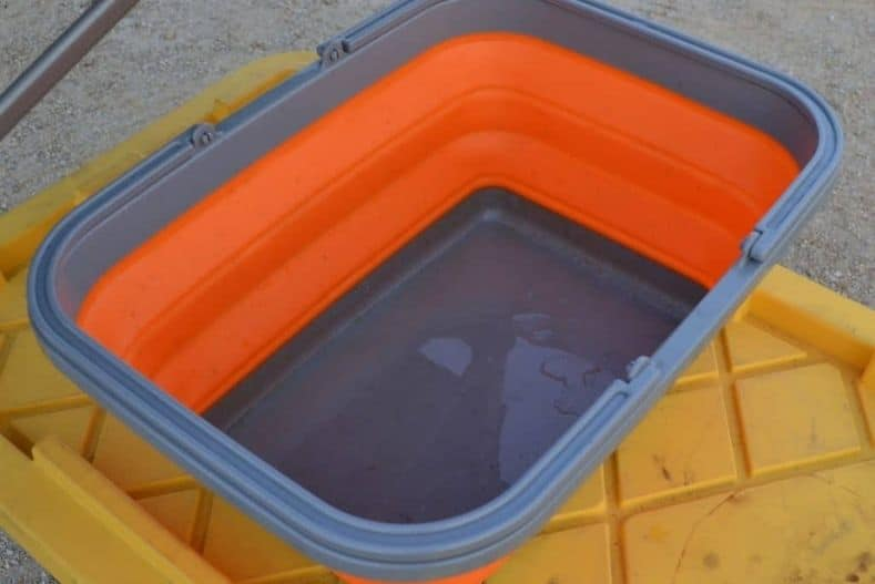 Orange collapsible wash basin for a list of truck camper accessories