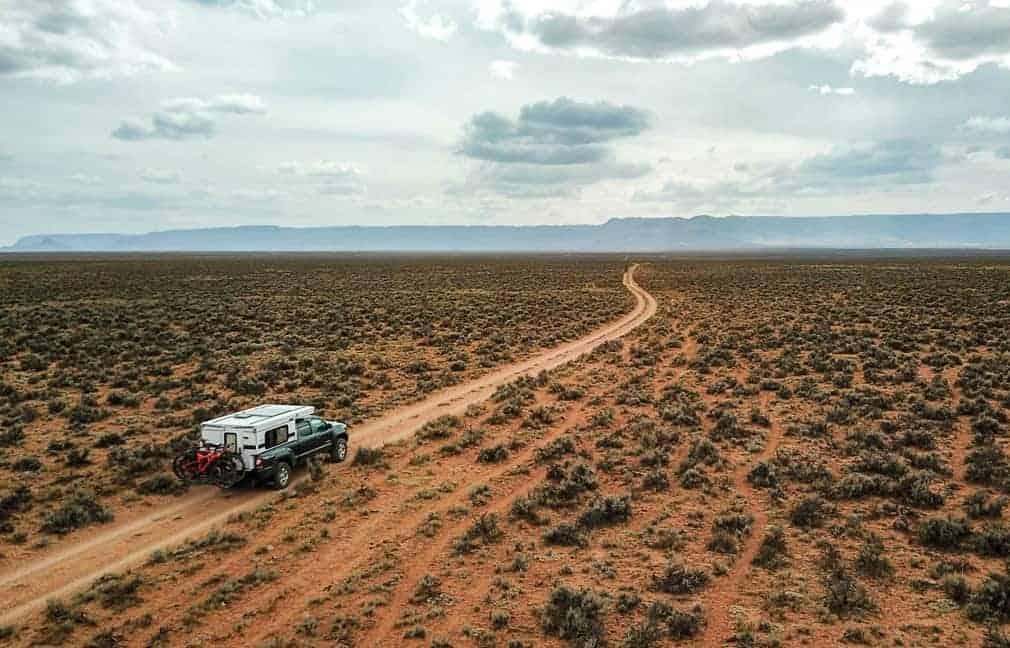 Fleet slide in truck camper for small trucks seen on a pickup driving through the desert