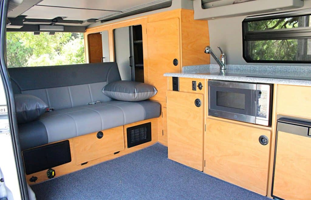 Interior of Ford Transit van rental with couch and kitchen
