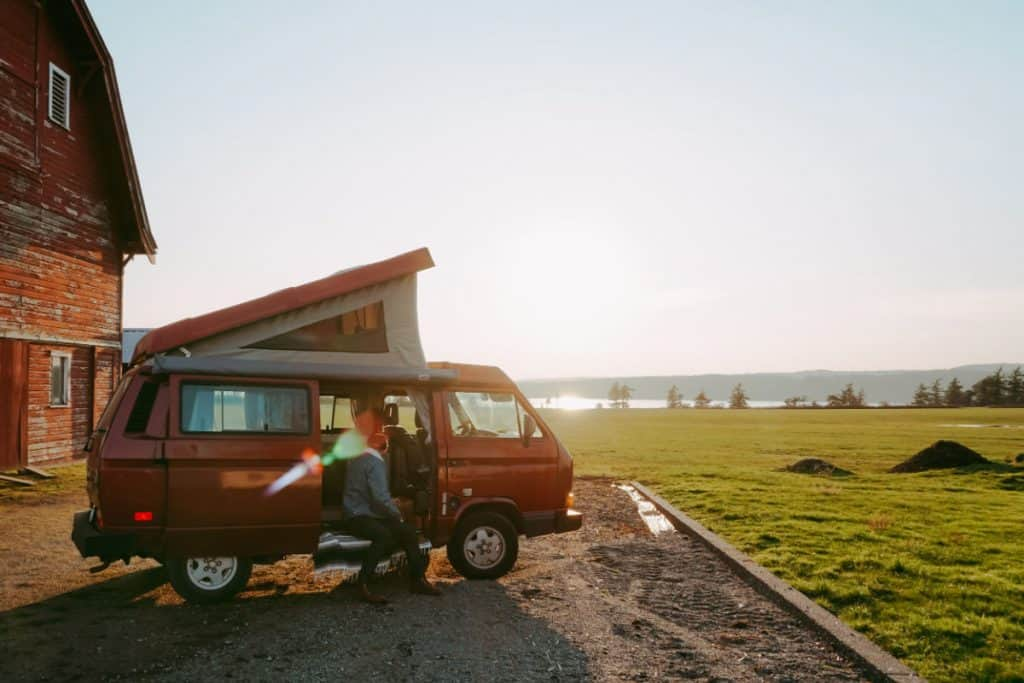 Red VW Vanagon camper rental for road trip parked on a farm