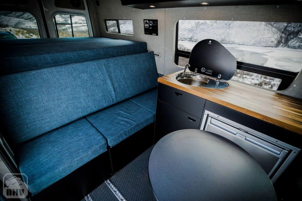 4x4 campervan interior with blue sofa and kitchenette