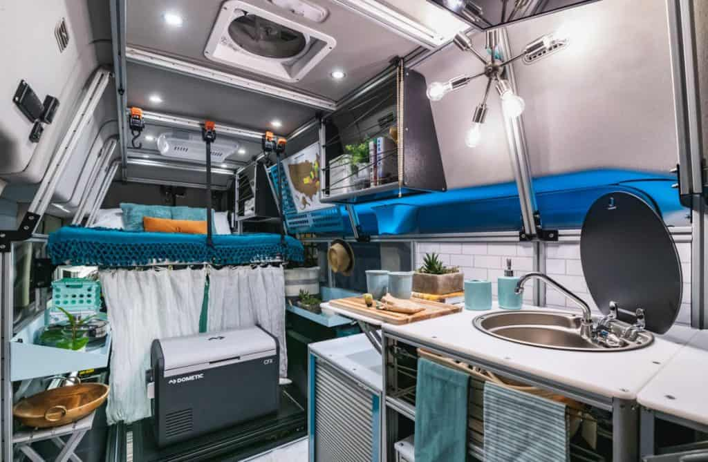 Interior of a 4x4 camper van for sale with kitchen, fridge and bed
