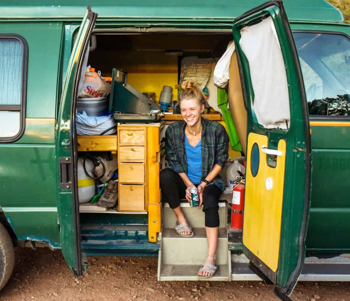 Woman sits inside a campervan during coviid