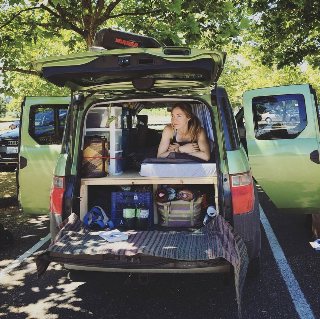 Honda Element SUV camper with woman lying on a platform bed