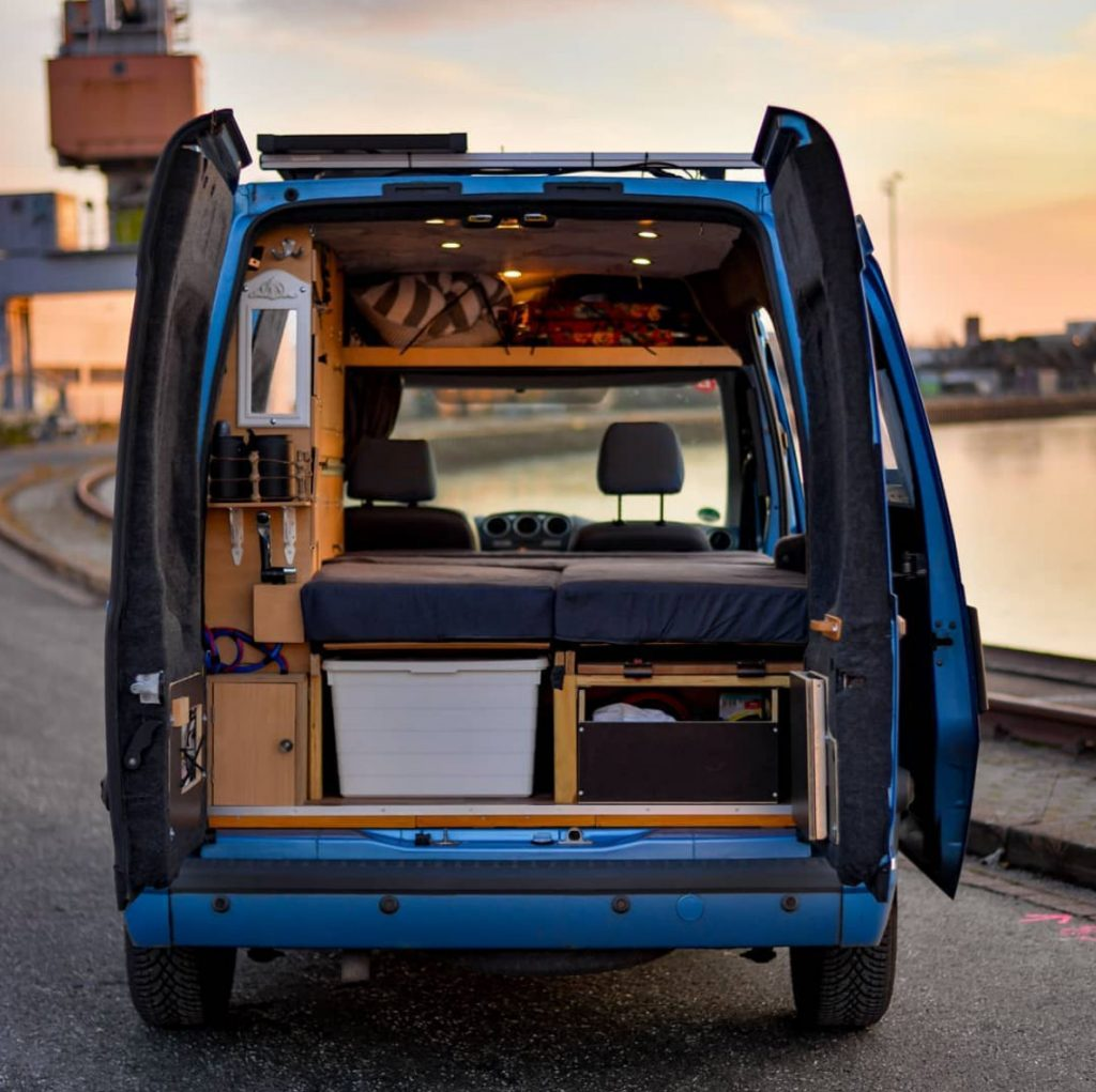 Interior of Ford Transit Connect camper with bed and storage