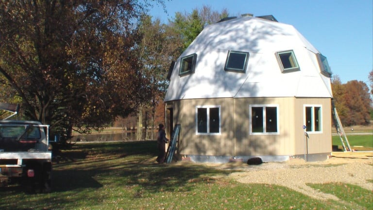 Econodome tiny house kit under $10,000 with white roof and tan exterior