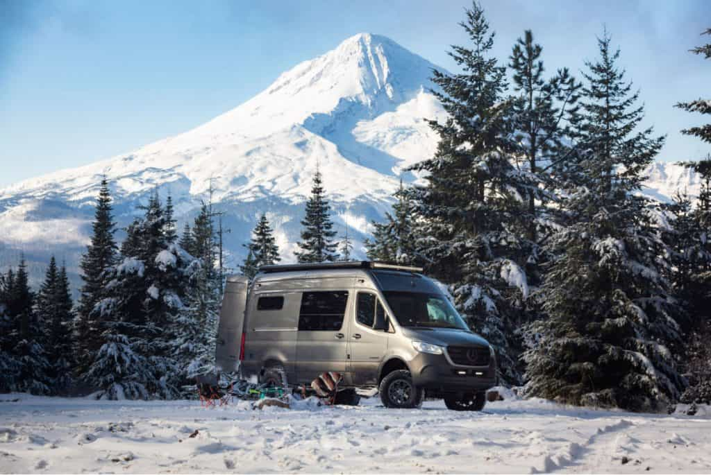 Gray Sprinter van parked in the snow by Outside Van conversion company