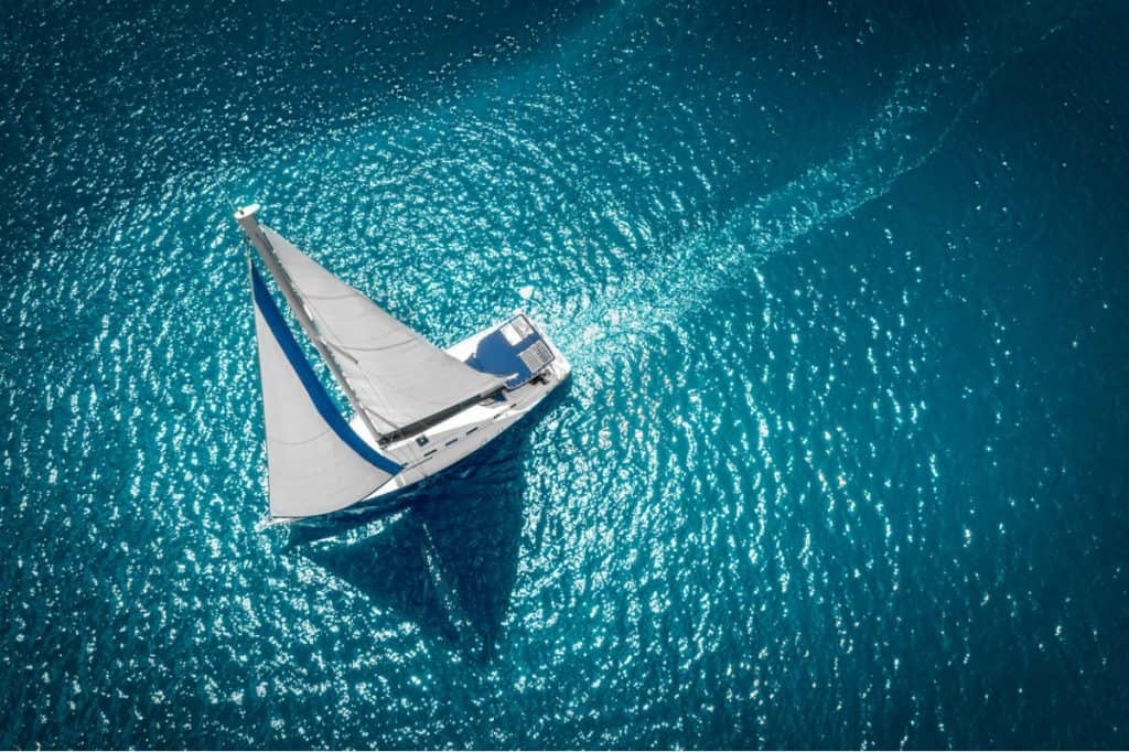 Small bluewater sailboat with sails up on the ocean