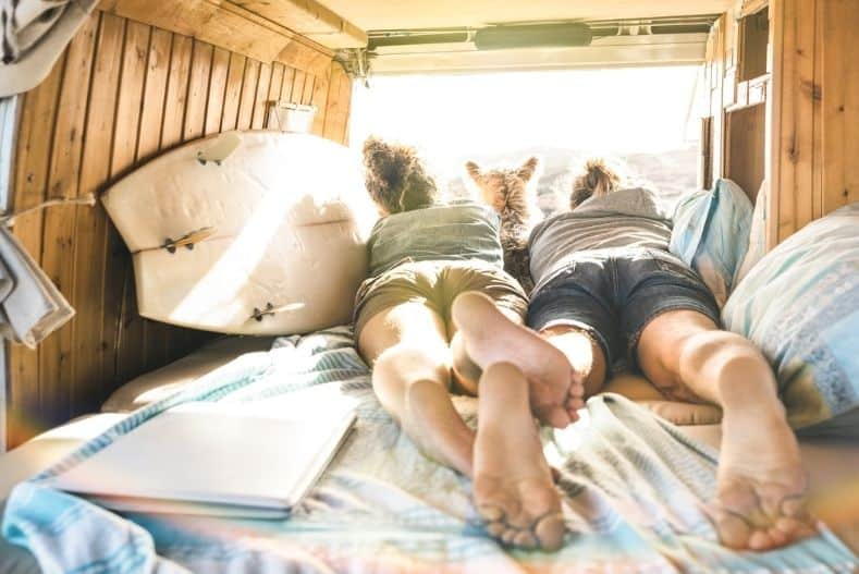 Couple lying in campervan with dog and surfboard