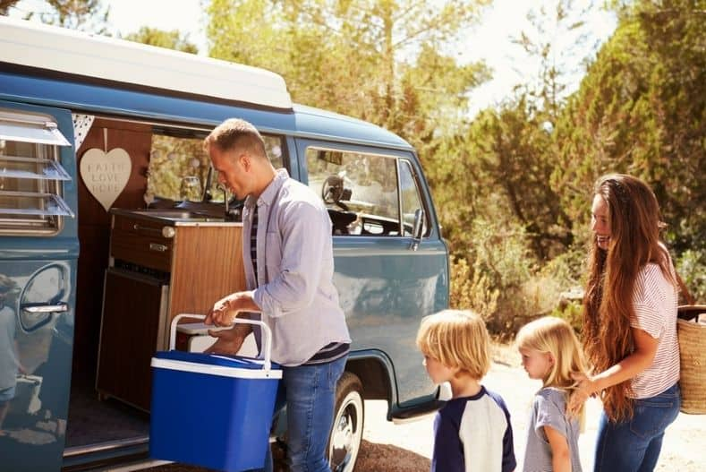 Family loading cooler into campervan
