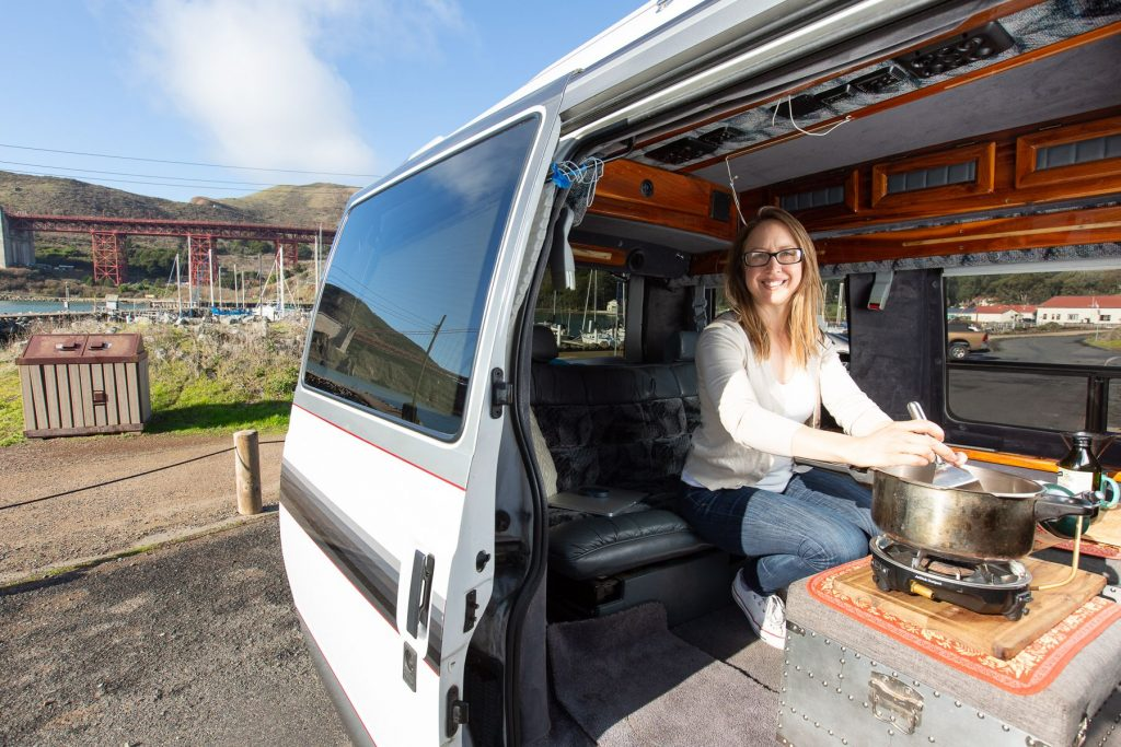 Woman cooking inside her stealth camper