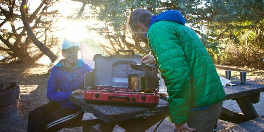 Two people at a camping table when camping in a national forest
