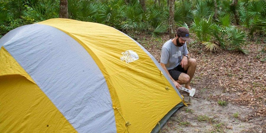 Man staking a tent when camping in a national forest