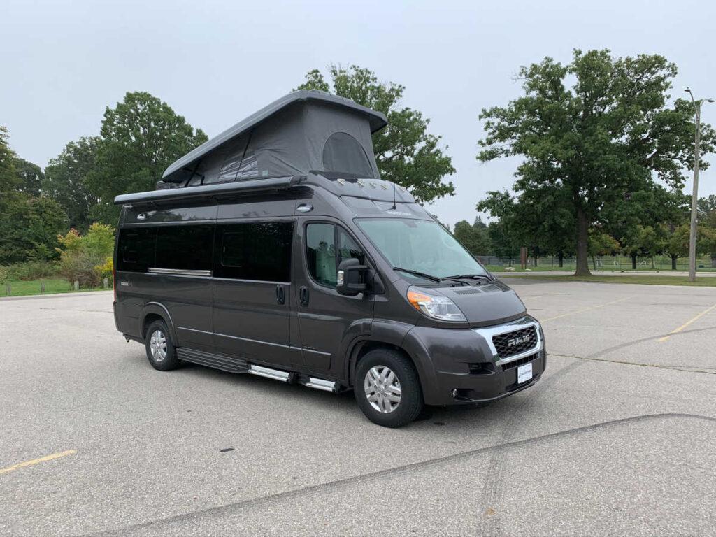 Gray Road Trek Zion popup van in a parking lot
