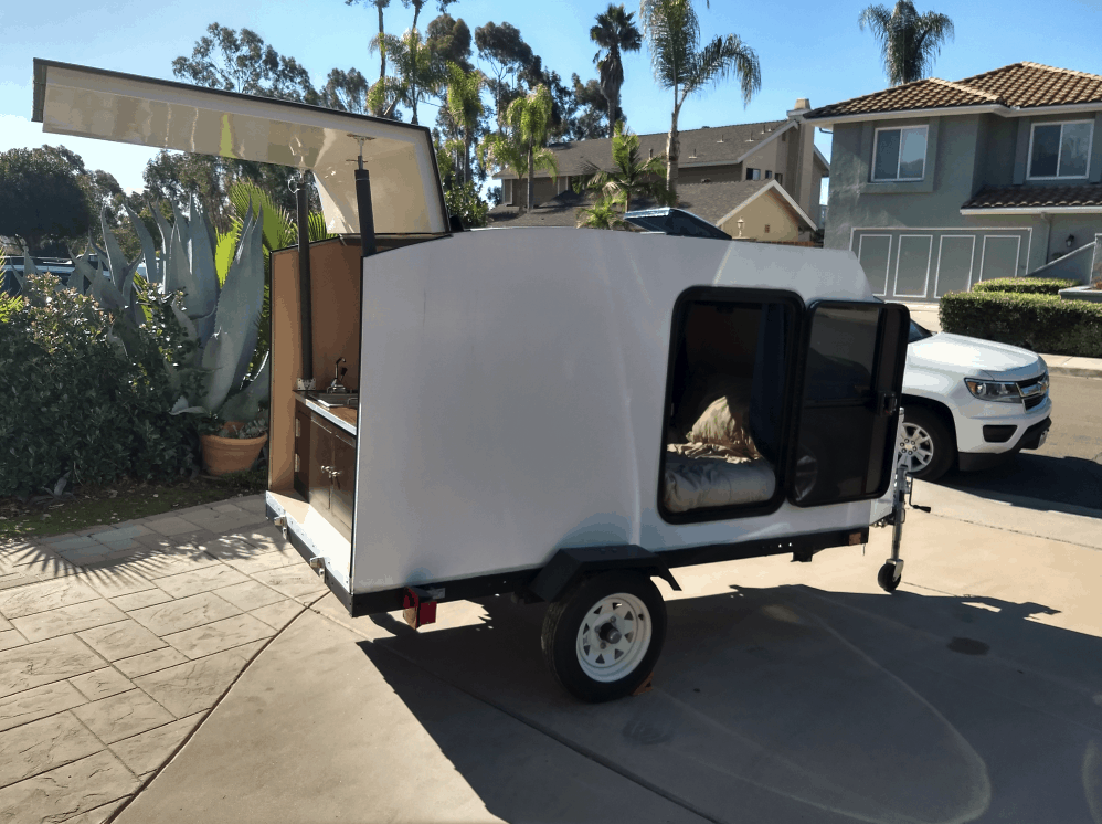 small camping trailer rental parked in a driveway