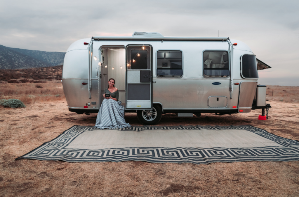 woman sitting in front of an Airstream travel trailer rental