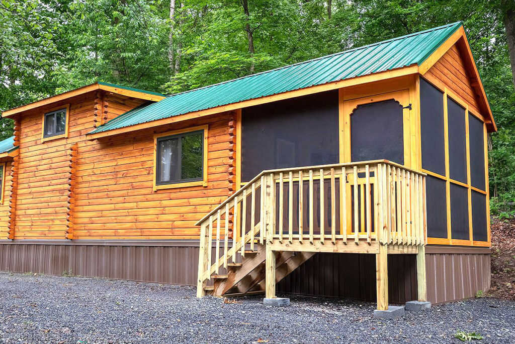Sierra tiny log cabin with green roof in the woods is one of our favorite tiny log cabins